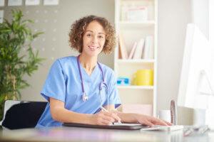 Smiling nurse at desk taking notes