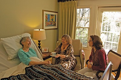 two women surrounding elder women in bed