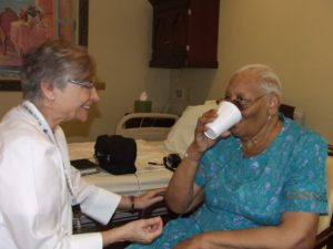 doctor assists patient as she takes drink
